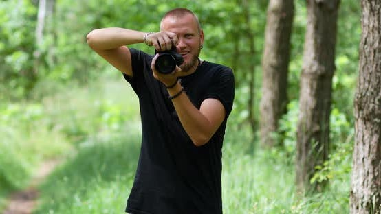Male Photographer Take Photo with a Professional Camera Outdoor