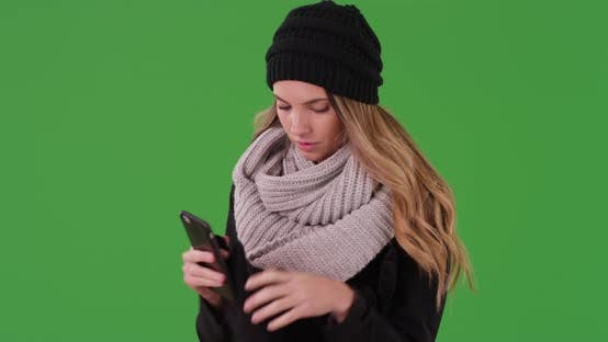 Thumbnail for Millennial girl removes her gloves to text on smartphone on green screen