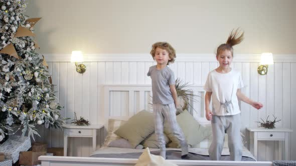 Thumbnail for Excited Little Kids Jumping on Bed in Room with Christmas Tree