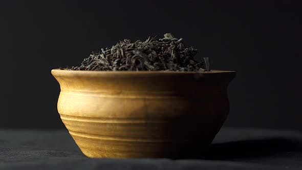 Close up view dry black ceylon tea leaves rotate in a clay bowl on black background