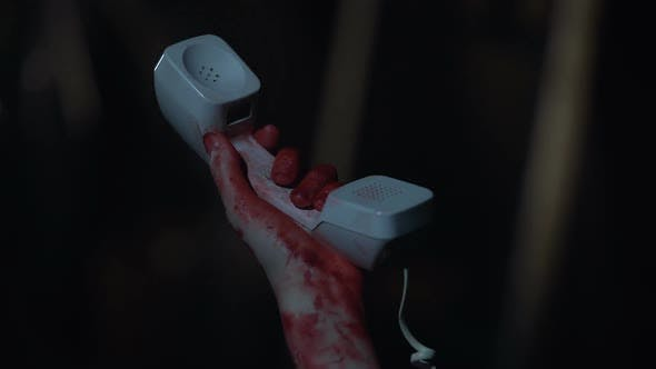 Cover Image for Trembling Hand Covered in Blood Holding Phone Receiver, Accident, Crime Scene