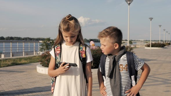 Thumbnail for School friends boy and girl walking and looking into smartphone.
