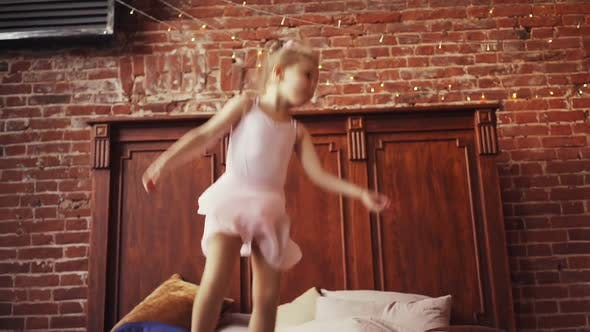 Cute Baby Girl Blonde Jumping on the Bed
