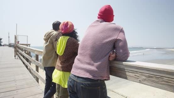Thumbnail for Junge Hipster Gruppe von multiethnischen Freunden stehend auf Pier Blick auf den sonnigen Strand