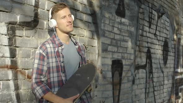 Thumbnail for Handsome male with skateboard listening favorite music on smartphone, hobby