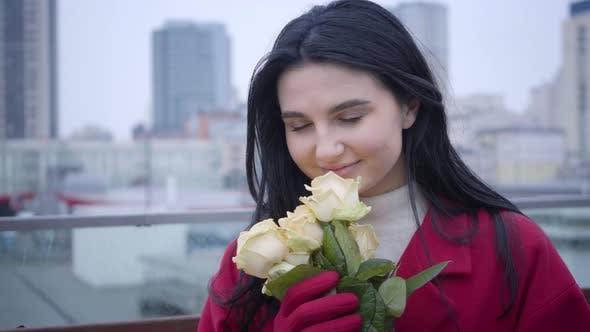 Thumbnail for Nahaufnahme Porträt von jungen kaukasischen frau mit schwarz haar riechend gelbe rosen und lächelnd