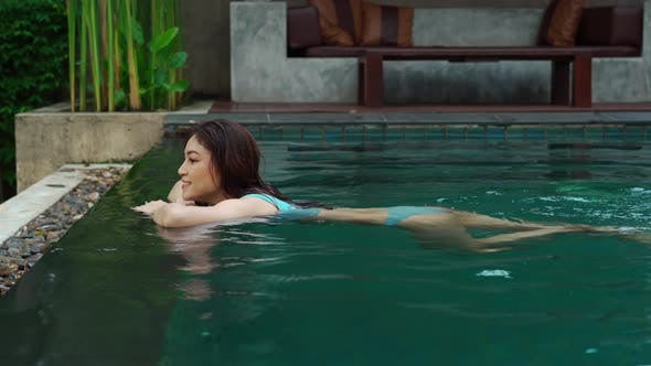 woman hold on to the edge of the swimming pool and splashing water with her feet