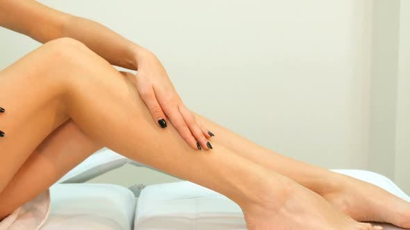 Thumbnail for Woman Strokes Her Leg on Massage Table