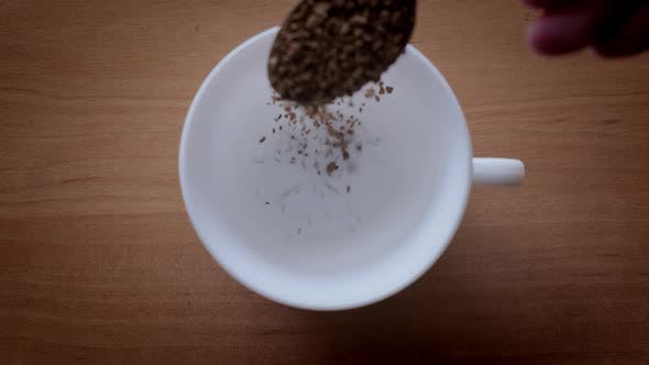 Granules of Instant Coffee are Poured Into a White Cup