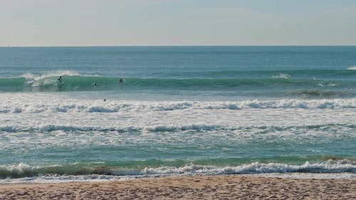 People surfing near the coast of the Atlantic Ocean on a sunny day
