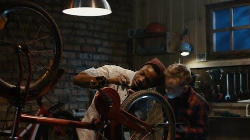 Mann lehrt ein Junge Fahrrad Wartung