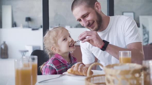 Cover Image for Cheerful Father Playing Airplane Spoon To Feed Cute Joyful Daughter with Chocolate. Portrait of