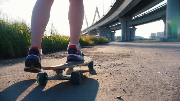 Thumbnail for Young Woman with Nice Legs Riding Skateboard Under the Bridge - Bright Sunlight