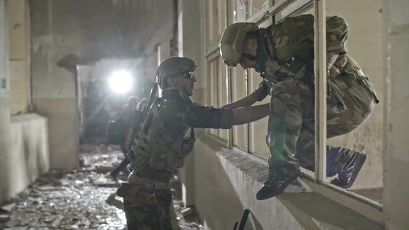 Soldiers with Firearms in Destroyed Building