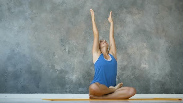 Cute Girl Practicing Yoga in the Studio, Sitting in the Lotus Position Concentrating