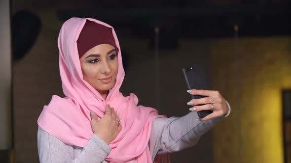 Thumbnail for Young Beautiful Woman in Hijab Doing Selfie on Mobile Phone Camera. Muslim Woman and Modern