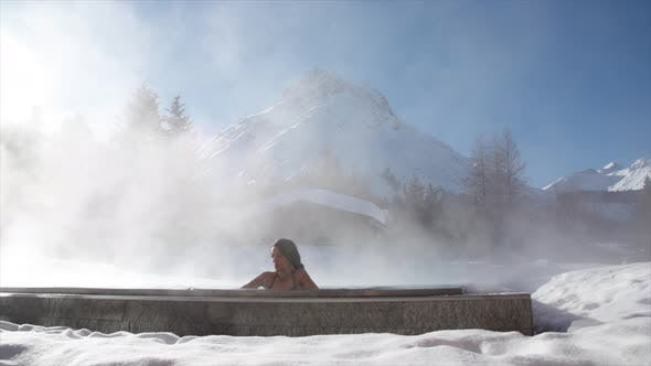 Thumbnail for A woman relaxes in a hot tub jacuzzi at a spa.