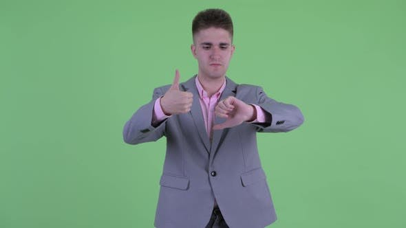 Thumbnail for Confused Young Businessman Choosing Between Thumbs Up and Thumbs Down