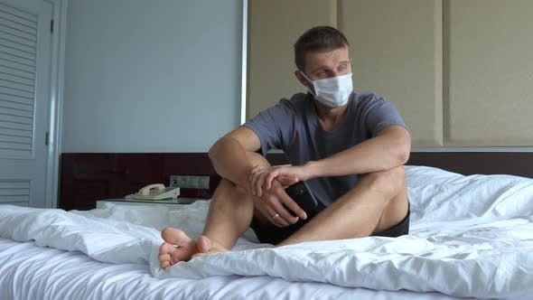 Lonely Depressed White Man Wearing Face Mask Sitting in Total Frustration on the Bed in His Room
