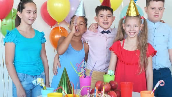 African-American Girl Blows Horn at Birthday with Friends