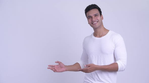 Thumbnail for Happy Young Handsome Indian Man Showing Something