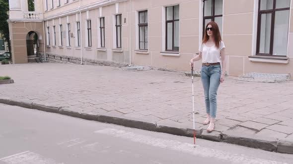 Thumbnail for Junge blinde Person mit langem Stock zu Fuß in einer Stadt