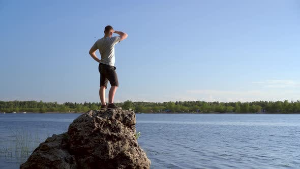 Thumbnail for A Young Man Stands on a Stone Near the River Admiring the Landscape. A Man in Nature.