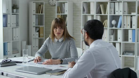 Thumbnail for Caucasian Businesswoman Speaking with Male Colleague and Taking Notes