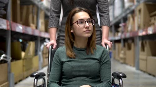 A Young Woman Is Sitting in a Wheelchair, Female Assistant Drives a Woman in a Wheelchair