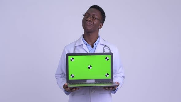 Thumbnail for Young Happy African Man Doctor Thinking While Showing Laptop