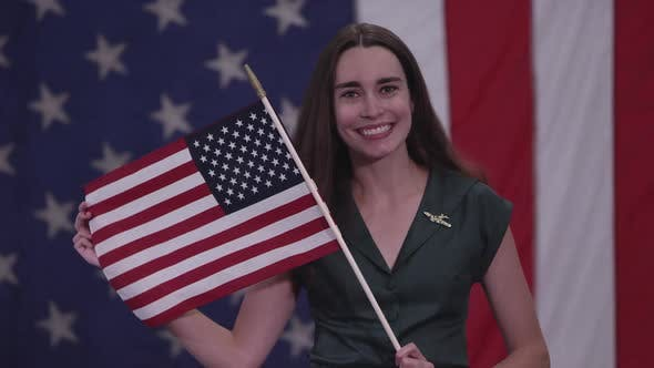Thumbnail for Young woman holding up American Flag and smiling