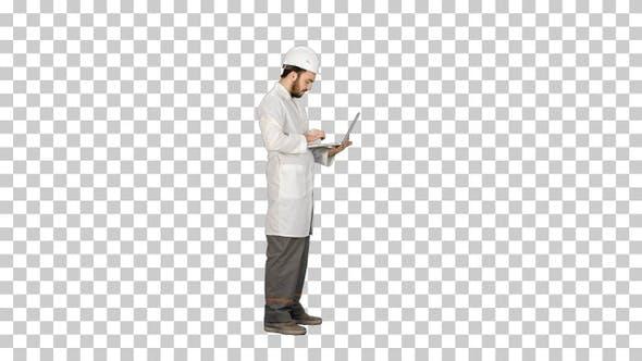 Portrait of an engineer in helmet using a laptop, Alpha Channel