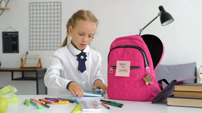 Little Girl Putting School Supplies in Backpack