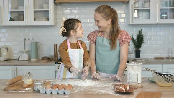 Cover Image for Happy Mother and Daughter Cook Together in the Kitchen, Throw Flour on the Table and Laugh. Have Fun