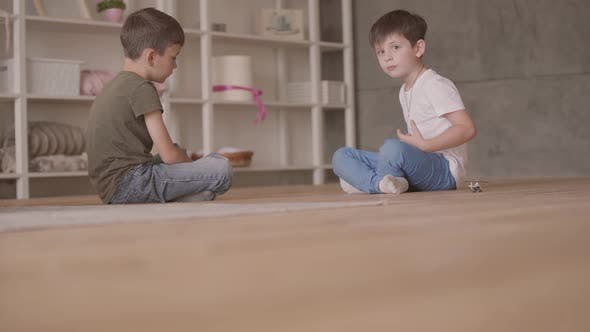 Thumbnail for Two Brothers Sitting on the Floor Playing with the Toy Car Sitting on the Floor at Home