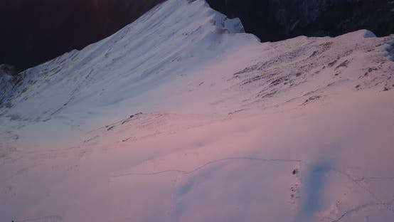 Thumbnail for Aerial drone view of snow covered Alps mountains in the winter at sunset.