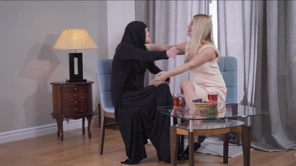 Thumbnail for Long Shot of Muslim and Caucasian Women Sitting at the Table at Home and Hugging