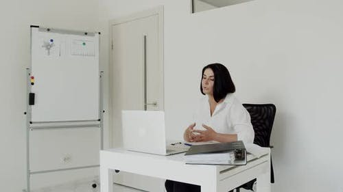 The Teacher Conducts an Online Lecture on a Laptop in the Office