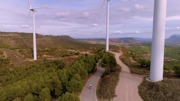 Thumbnail for Cyclist Rides Between Turbine Wind Farm at Sunset