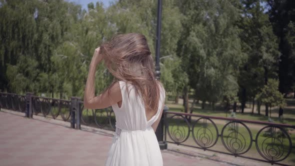Thumbnail for Cute Young Girl Wearing Sunglasses and a Long White Summer Fashion Dress Walking Outdoors