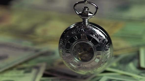 Thumbnail for Silver pocket watch and dollars, time is running out like money. Time management