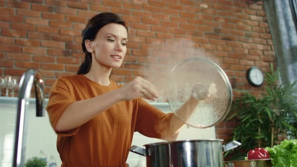 Thumbnail for Woman Cooking Healthy Food in Kitchen. Girl Salting Hot Meal in Boiling Pot.