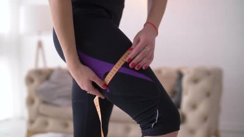 Midsection of Fit Woman Measuring Her Thigh