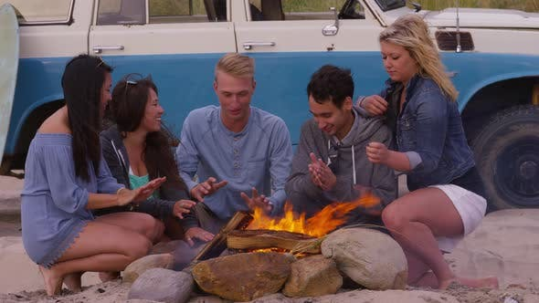 Thumbnail for Group of friends at beach sitting by fire