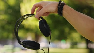 Male Hand Holding Big Headphones in a Park