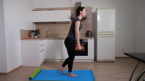 Sporting a Young Girl t Doing an Exercise on a Blue Yoga Mat with Dumbbells