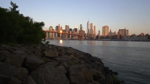 SLOW MOTION Downtown Manhattan View Close to Water with Brooklyn Bridge in Beautiful Sunrise