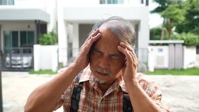 Bearded old man has a headache
