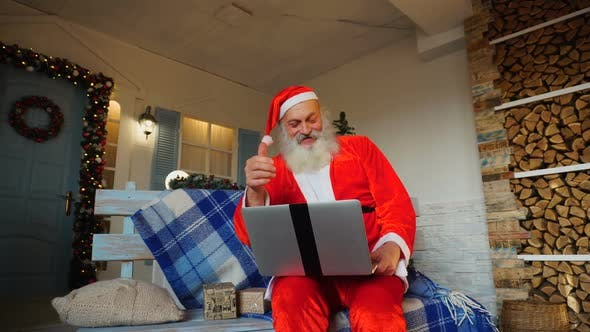 Thumbnail for Funny Santa Claus Showing Thumbs Up and Working with Laptop.