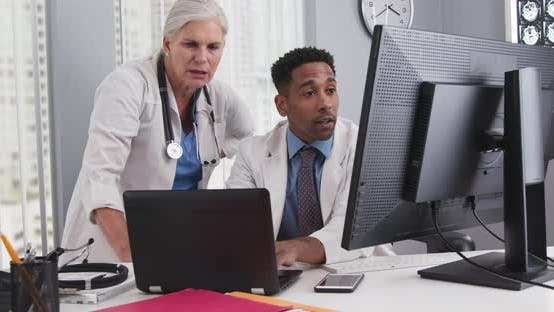 Thumbnail for Close up of two doctors looking at computer monitor comparing notes